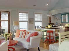 Unique Kitchen Pendants for Beach Homes - Love the splash of coral accents and the colorful barstools!