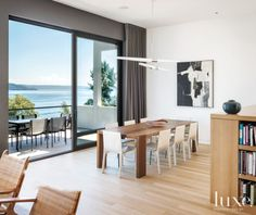 The dining room enjoys water views and is anchored by a custom table, with pendant lighting by David Weeks Studio and chairs by Matteograssi. The painting is by Paul Horiuchi. Furniture by Richard Schultz sits on the terrace.
