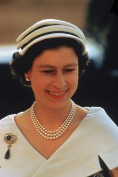 Queen Elizabeth II in Sweden, wearing a lot of pearls and an interesting hat.