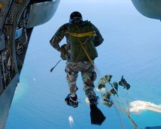 """Santa Rita, Guam (Oct. 25, 2001) -- An Explosive Ordnance Disposal Technician assigned to Explosive Ordnance Disposal Mobile Unit Five (EOD MU-5), leaps from a CH-46 """"Sea Knight"""" helicopter during a static line water parachute jump over Apra Harbor, Guam. U.S. Navy photo by Photographer's Mate 2nd Class Marjorie McNamee. (RELEASED)"""