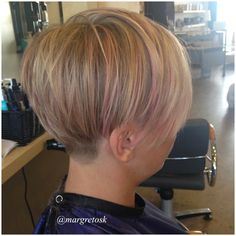Short women's hair with undercut and layers.  Blonde hair with pastel pink highlights