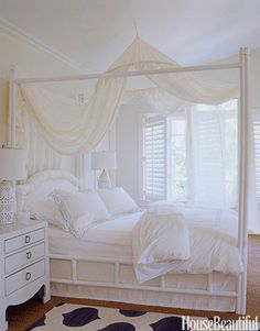 The teenage daughter's dreamy white-on-white bedroom is the essence of serenity. Walls, ceiling, and trim are all in Benjamin Moore's Seashell. Mosquito netting drapes the painted bamboo bed. Lamps from Linens n' Things.   - HouseBeautiful.com