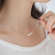 A delicate starburst necklaceGorgeous stars bunched together with one little star following like a constellation in the sky. The little star on the side is double sided with cubic zirconia each side - so even when it's turned around it still shines on your neck. Very delicate and so sweet little necklace. We have matching two-way earrings - please see related product.Brass, cubic zirconia and gold plated, rhodium platedEach star size is about 4m. 43.5mm total length (there is about 2cm…