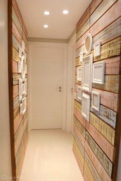O corredor de 3,30 m² possui painel de madeira de demolição com resto de tinta e quadros laqueados brancos. Projeto de CAS Arquitetos Associados.