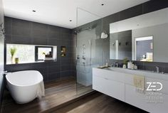 Interior: Large Bathroom Design With Wooden Floor And Dark Gray Tiled Walls, Features A White Freestanding Bathtub, A Floating Vanity And Frameless Mirror: Urban Family Loft Interior Design