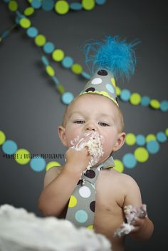 1st birthday cake smash on seamless paper backdrop in thunder grey with blue and green paper dot garland.