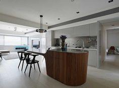 moderne küche mit grauen lackfronten und kochinsel aus holz in futuristischem…