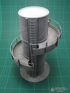 Fuel Storage Towers: elevated twin level towers with climbing rungs for movement access.    Materials: pringles cylinder, foamcore, plastic card and angle, heavy duty staples (rungs).