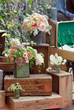 My main Inspiration photo (ignore the top arrangement, too salmon) - Lovely Flowers in Rustic Containers on Wood Crates. Tones can go peachy, muted pinks and creams, and could have a few pops of  brighter pink or plum in places.