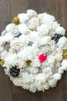 How to make a pom pom rug! This soft, scrumptiously squishy DIY pom pom rug takes very few skills to create and is a great way to use up a bunch of scrap yarn! Click for full tutorial.   MakeAndDoCrew.com