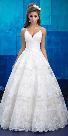 Sheer chiffon stripes create a tiered effect along the skirt of this lace ballgown.