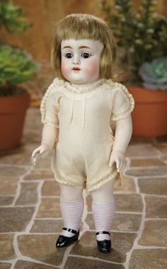 "11""-Large German All-Bisque Doll by Kestner~~~11"" (28 cm.) One-piece bisque head and torso of chubby child, brown glass sleep eyes, dark eyeliner, painted lashes and brows, accented nostrils, open mouth, four porcelain teeth, brunette mohair bobbed wig, loop-jointed bisque arms and legs with painted ribbed stockings to the knees, black one-strap shoes, muslin chemise.  Marks: 150 6 (head and legs). Comments: Kestner, circa 1900."