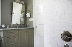 Gorgeous gray green bathroom design with gray green bathroom cabinet, white carrara marble counter top, rectangular pivot mirror, gray green walls paint color, subway tiles, double sconce and polished nickel faucet.