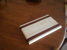 "Maple, Walnut and Bubinga Cutting Board - finished with mineral oil.  Cutting board size is approx. 10.5"" wide x 16"" long x 1 ¼"" thick.  These are edge-grain cutting boards, and will perform well for all cutting activities.  Glue up is done using Type-III waterproof glue, and board is sanded to a 320 grit finish. Time is taken to raise the grain before the final sanding ensuring a smooth finish.  (Care and Maintenance – use a small amount of soapy water and a sponge to wipe clean. For any…"