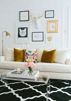 White sofa with gold velvet pillows, acrylic coffee table and black and white diamond pattern flat weave rug.