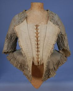 PLAID SILK CARACO JACKET, c. 1770. Narrow sea green vertical stripe over cream and tan horizontal bands, open neck, short angled sleeve, pleated peplum angled at front, all trimmed in wide self furbelows, looped silk cord and tiny tassels, lined in linen with adjustable lacing closure and front stays. B-33, W-24, L-21 (whitakerauctions)