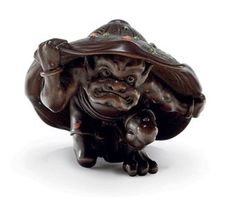 A Wood Netsuke   Signed Soko to, Meiji Period (late 19th century)   Of an oni cowering under a hat, stained cowhorn inlays, So School