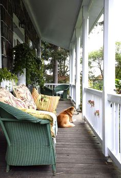 Green couch with yellow pillows on front porch with white railings. Robin Stubbert Photographer - Garden Photography