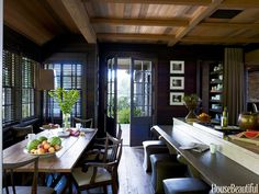 Pine walls throughout the house are finished with a mix of Jacobean and Ebony wood stains by Jan Hale Studios. Espresso-color wood window blinds with chocolate-brown tape harmonize with the room's dark tones.