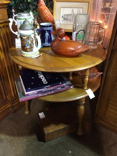 """We love the vintage feel of this cool round end table! It has two tiers, so the underneath shelf is perfect for magazines or remotes. The top is nice and large and could hold a lamp, picture frame and floral! This piece could be used next to a sofa/chair in a family room or even as an accent table in a bedroom. Quite versatile! Dimensions are 26"""" x 25""""."""