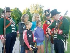 Penetanguishene family celebrates rich history - Members of the Thompson's Company of the 2nd Regiment of York Militia War of 1812 re-enactment group explain the workings of a 19th-century flintlock musket to Wendy Stephenson, second from left, Braydon Thompson, Linda Thompson and Kylie Thompson.