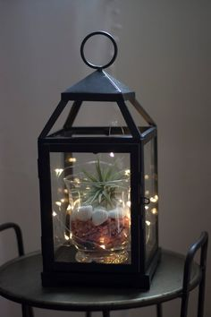20 Impressive Terrarium Designs for Your Home Decoration Simple lantern terrarium with black iron lantern, succulent, white gravel and decorative lighting for your home decor