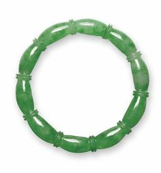 A VERY IMPORTANT JADEITE BANGLE - The carved circular jadeite band of rich emerald green colour and high translucency, depicting as a circle of lotus root. Christie's.