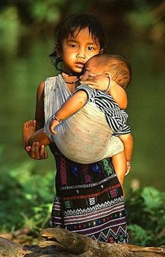 In parts of our world this is how a little girl's world is... a child caring for and raising her sibling. Beautiful photo.