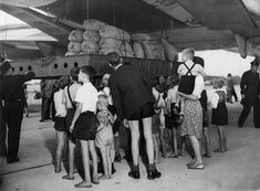 German youths watch as a US C-74 Globemaster plane at Gatow airfield on August 19 begins to unload more than 20 tons of flour from the United States during the Berlin Airlift, 1948-49.