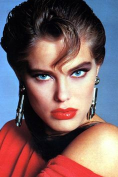 Huge 80's makeup, bold dark eyes and red lips
