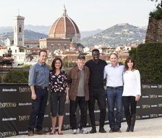 """The cast and crew of """"Inferno"""" pose for the press - May 11, 2015.  L to R: Tom Hanks, Sidse Babett Knudsen, director Ron Howard, Omar Sy, author Dan Brown, Felicity Jones."""