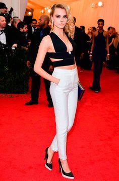 Street style look Cara Delevingne com cropped preto, calça branca a escapin.