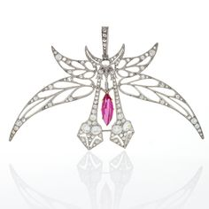 A French Art Nouveau platinum and 18 karat gold pendant/brooch by Henri Vever. The pendant/brooch has 35 old European-cut diamonds, 94 rose-cut diamonds and 1 hanging marquise-cut pink topaz.