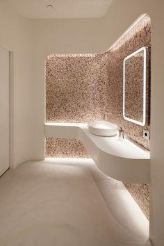 Design bagno ultramoderno con rivestimento in mosaico e particolare illuminazione