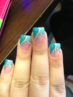 Teal and blue acrylic nails with jewels on the side