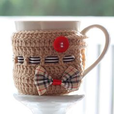 Crocheted Burberry Mug Cozy. Cup size: Diameter Height You'll need: no 4 crochet hook; medium no 4 yarn; Ribbon of your choice to make bow; Ribbon about 7 mm width; button about diameter - good inspiration Crochet Coffee Cozy, Crochet Cozy, Diy Crochet, Crochet Crafts, Crochet Hooks, Crochet Projects, Coffee Cozy Pattern, Mug Warmer, Crochet Home Decor