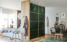 Tmavohnedá skriňa s posuvnými dverami použitá na predelenie miestnosti na spálňu a obývaciu izbu.