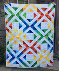 This beautiful rainbow quilt has 32 different colors in it. This quilt is approximately 54 x 70 inches. Its made from high quality 100% cotton fabrics. The back is a modern gray fabric with white dots. It is professionally longarm quilted with an all over meandering design. The