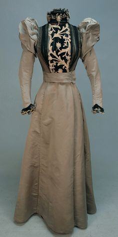 1890s two-piece grey faille having boned bodice covered in pleated black chiffon with sequins and crystal beads, black chiffon insert with cream tape lace, sleeve having twin puffs, ruffled collar with back bow and ruffled cuff. Undecorated silk skirt lined in polished cotton with velvet hem band.