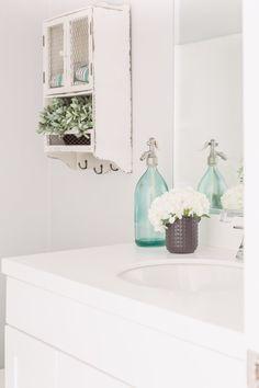 PURE SALT INTERIORS // ARIA PROJECT // BATHROOM // vintage shelf, potted plants, flowers, white counter...