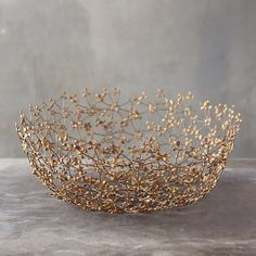 A unique accent for indoor spaces, this display bowl is made from a firm but flexible latticework of iron flowers and brass.- Iron, brass- Dust with d
