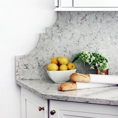 Base cabinets that don't line up with the uppers are united via a full height decorative quartz splash evocative of a built-in hutch.