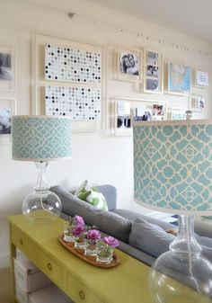 One way to avoid drilling more holes into the wall - opt for a floating gallery. The designer used Ikeas Diginet curtain wire system to suspend the handmade frames. I also love the table behind the sofa in this picture and the overall color scheme.