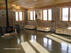 """The Cordwood Education Center on a sunny day. Notice how the sun reaches deep into the building for passive solar gain. This building is used daily as a classroom by the Merrill Schools and is a fine example of best practices with alternative construction. Note that the ceiling is wood (harvested on site) and has a 3/12 pitch which """"opens"""" the space. and YES, that is a Badger on the shelf in the top right hand corner www.cordwoodconstruction.org"""