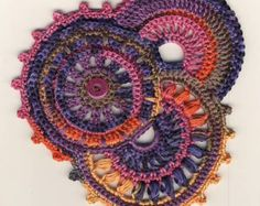 I wrote this tuto to help you to begin freeform crochet. You'll see how you can add extentions to a circle motif so that you can make a freeform crochet scrumble. You'll know how to navigate from one point to another, and begin a new stitch, as well as how to add texture to a simple crochet stitch. It contains 16 pages including 30 step by step photos as well as written instructions to show you how to achieve this scrumble. A crochet beginner knowing only basic stitches can easily obtain a…