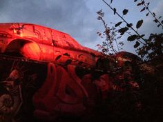 Artistic shot of a car covered in graffiti taken at sunset