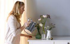 Femme en train de remplir d'eau un vase avec des fleurs.
