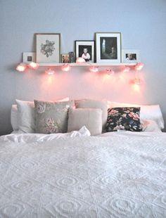 Flower lights hanging from floating shelf over bed.