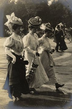 June 3, 1906 Three women walking briskly along on he Champs Elysees, perhaps mother, sister and daughter. Is the ground a little wet underfoot, hence the umbrellas?