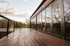 Large timber deck with bifold doors to inclose the outdoor living space, perfect during the winter months. Space created by ACT Decks